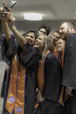 students taking a group selfie in graudtion gowns