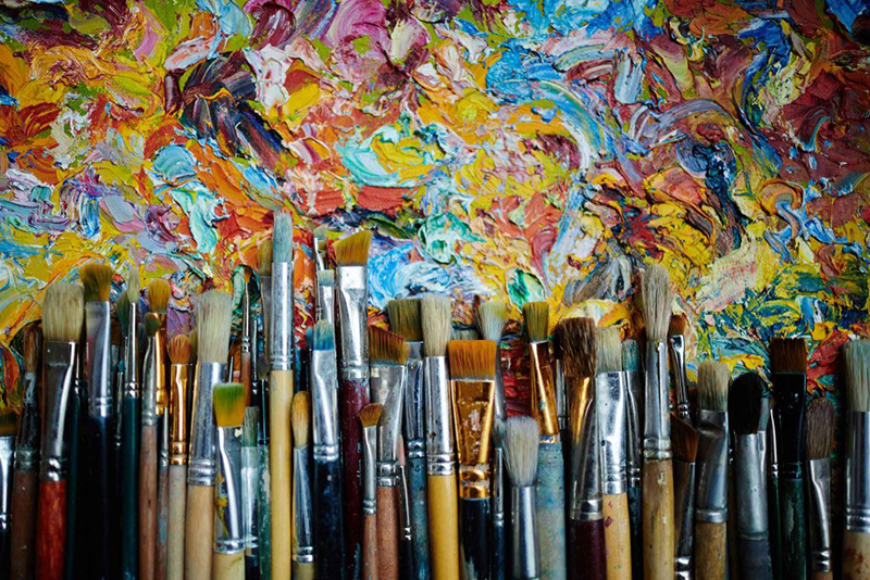 A row of paint brushes at the bottom with multiple brush strokes of many colors above