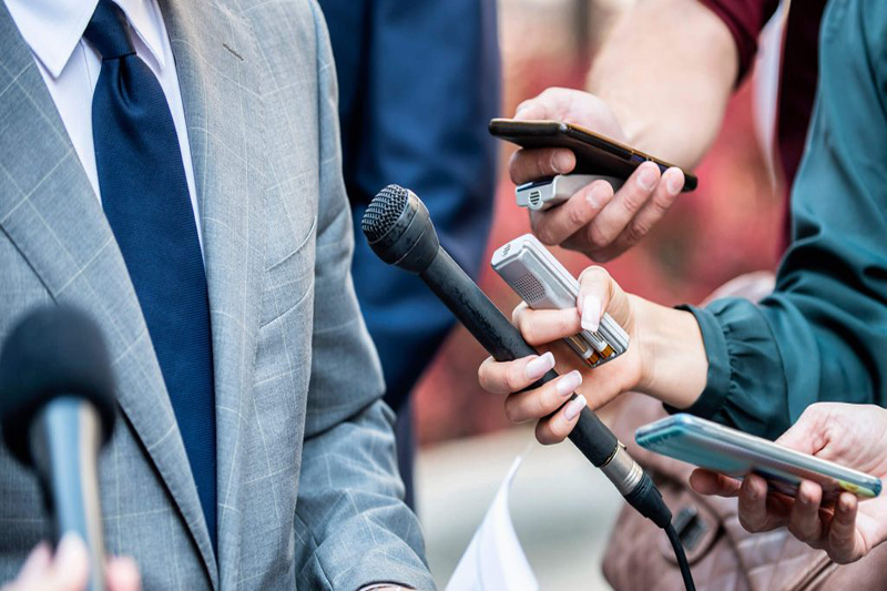 Figure in coat and tie being interviewed with recording devices pointed towards them