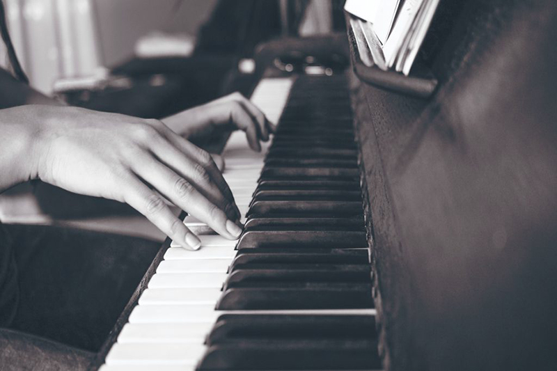 Hands playing a piano in black and white
