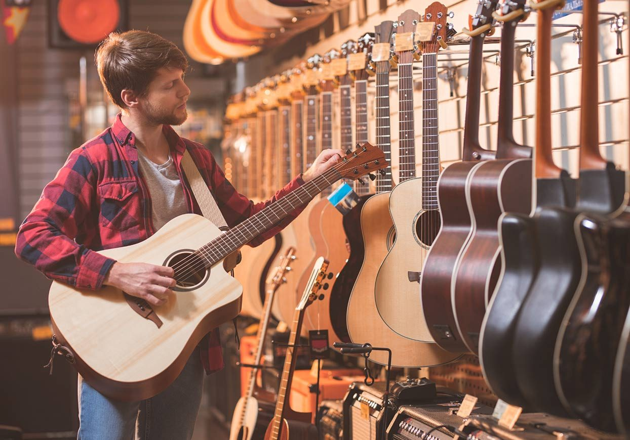 man with a guitar in a music store