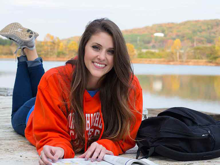 Girl Studying Outside on a Pier Beside Parris Lake