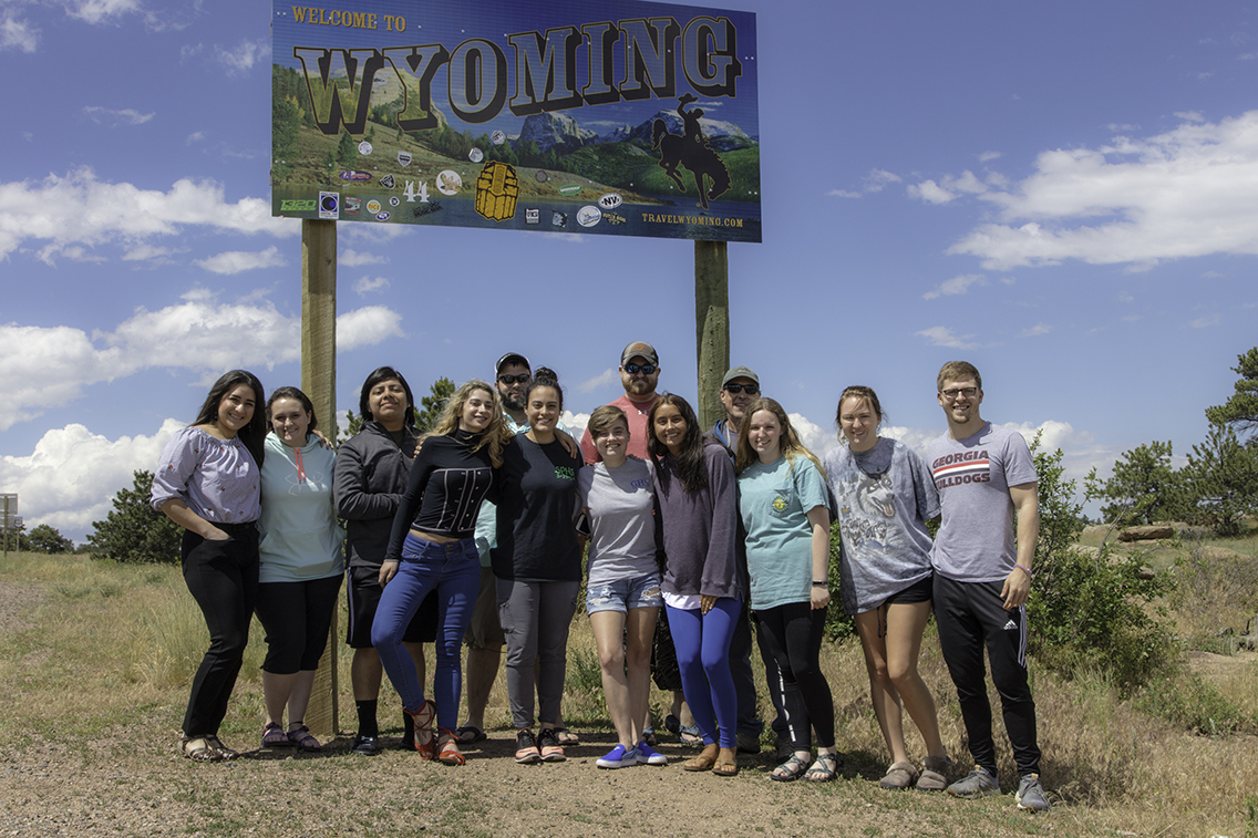 Students in front of Welcome to Wyoming sign