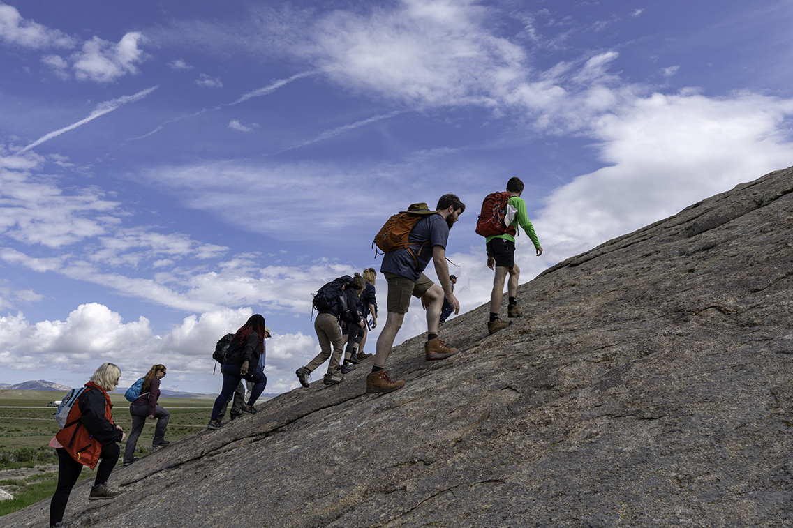 Students climbing Independence Rock
