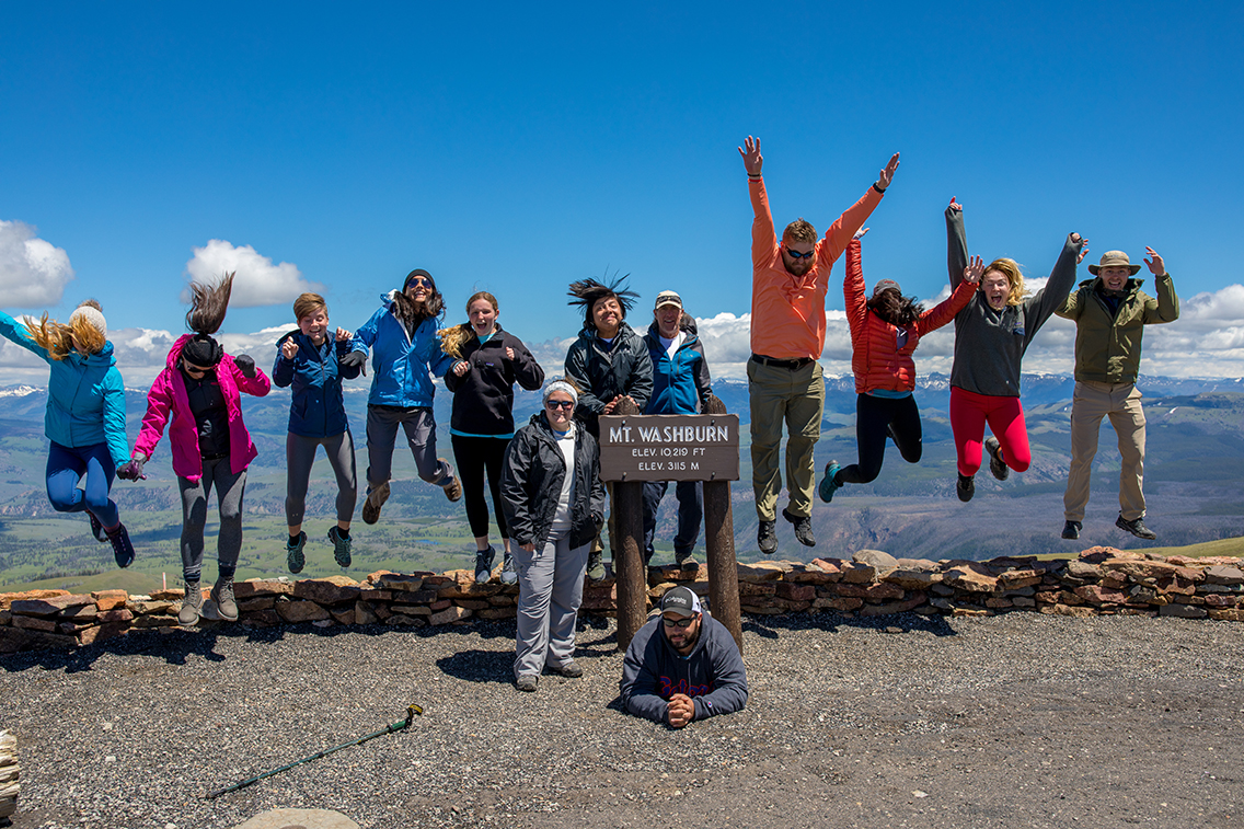 Students jumping on top of Mount Washburn